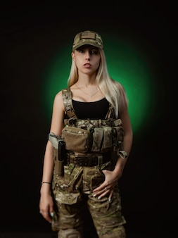 A sexy girl in military airsoft overalls poses with a gun in her hands on a dark background