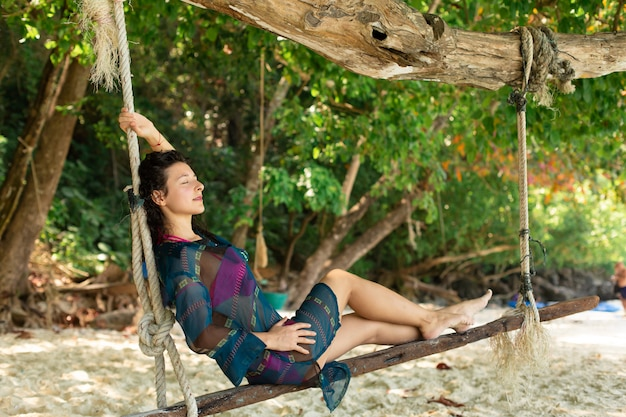 Sexy girl model resting while riding on a swing tied to a tree on a tropical island.