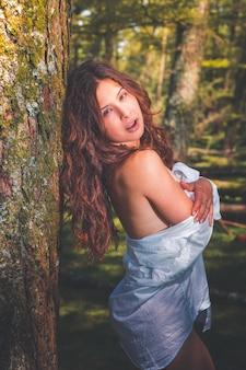 森でポーズのセクシーな女の子