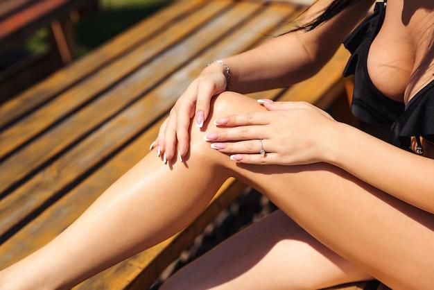 彼女の足に日焼け止めローションを置くセクシーな女の子をクローズアップ