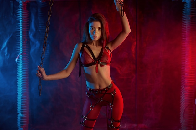 Sexy girl in red bdsm suit holding on to chains, abandoned factory interior. young girl in erotic underwear, sex fetish, sexual fantasy