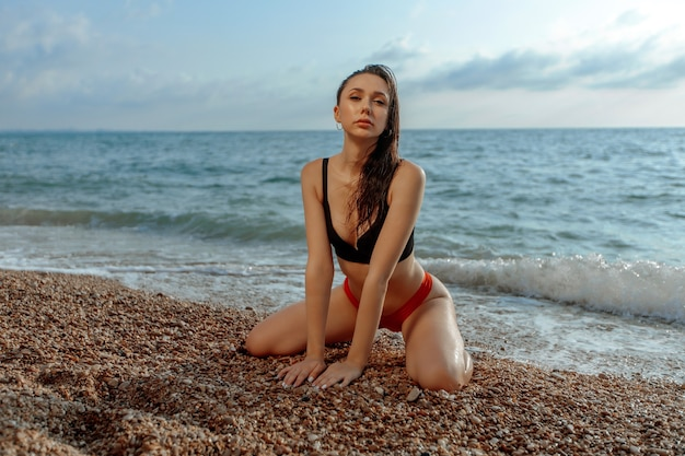 Sexy girl in a red swimsuit is sitting on the beach
