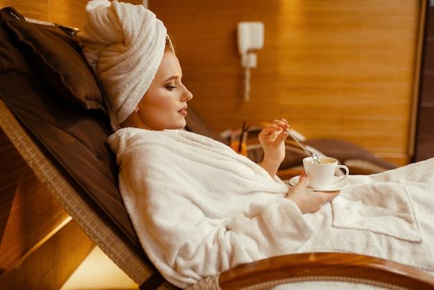 Сексуальная девушка расслабляющий с чашкой кофе в кресле спа
