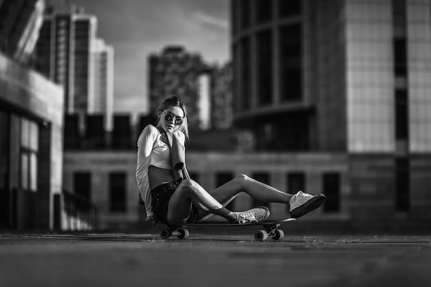 스케이트 보드에 앉아 섹시 한 소녀입니다. 고품질 사진