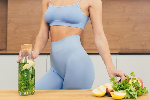 섹시한 여자, 운동가는 집에서 과일과 채소의 신선한 음료를 준비합니다