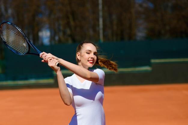 コートでテニスラケットを保持しているセクシーな女の子のテニス選手。若い女性はテニスをしています。