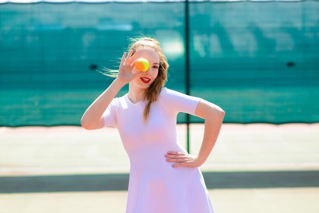 Сексуальная девушка-теннисистка держит теннисную ракетку на корте. молодая женщина играет в теннис.