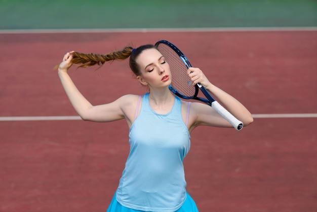 コートでテニスラケットを保持している白いドレスとかかとのセクシーな女の子のテニスプレーヤー。若い女性はテニス、スポーツをしています
