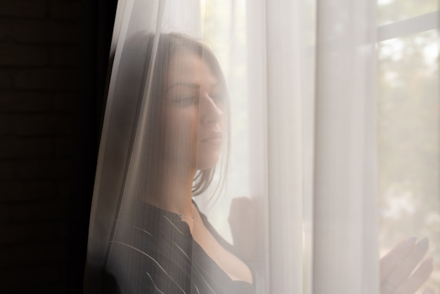 A sexy girl, in an unbuttoned shirt, behind a curtain, looks out the window. for any purpose.