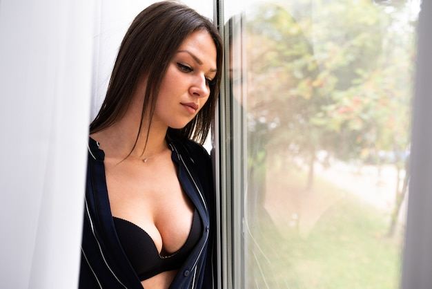 Sexy girl, in an unbuttoned shirt, looks out the window. for any purpose.