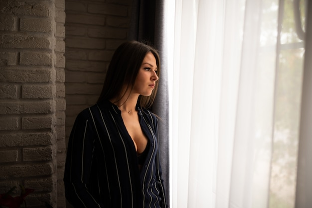 A sexy girl, in an unbuttoned shirt, stands near the window. for any purpose.