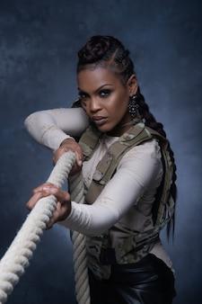 Сексуальная девушка в жилете в стиле милитари позирует с веревкой и смотрит в камеру в студии
