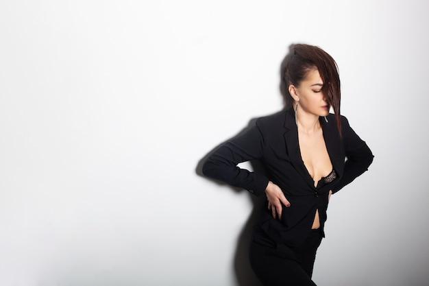 Сексуальная девушка в модном черном пиджаке показывает свои длинные красивые здоровые волосы в модной позе