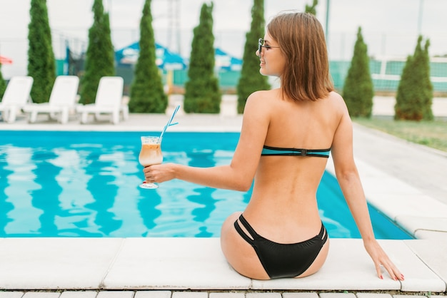 Sexy girl with cocktail near the pool, back view