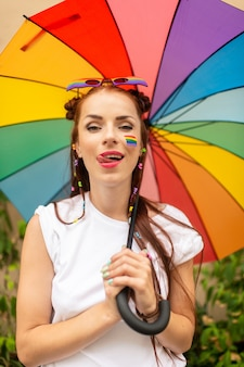 Sexy girl with colorful umbrella with painted lgbt flag on her face posing outdoor.