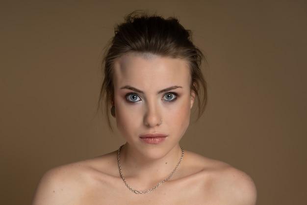 Сексуальная девушка с гетерохромией, выразительно смотрит в камеру, пирсинг носа и затычку в одном ухе, странная прическа. с потрясающим профессиональным макияжем и серебряной цепочкой на шее бежевый фон