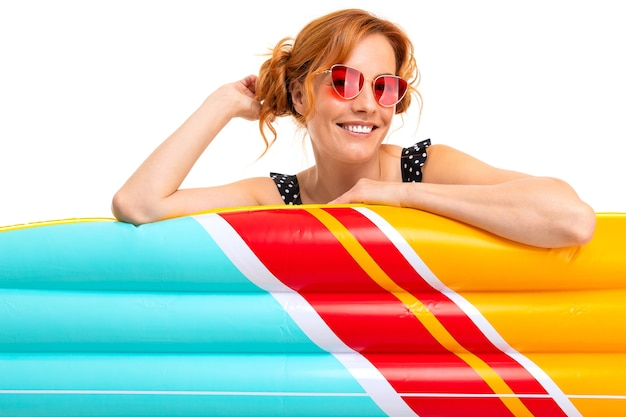 白い背景の上の休暇で膨脹可能な水泳サークルとマットレスを持つセクシーな女の子