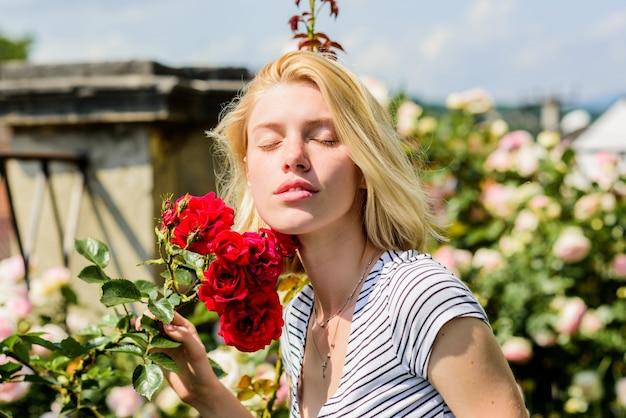 빨간 장미와 함께 섹시 한 여자입니다. 정원에서 금발 머리를 가진 아름 다운 여자입니다. 자연미. 스파 및 스킨케어. 여름과 봄 공원 자연입니다. 장미꽃 냄새. 향수. 아침에 휴식.