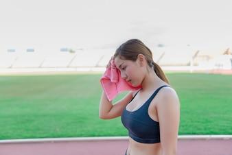 セクシーな女の子は、ジョギングが終わった後に汗を拭くために停止