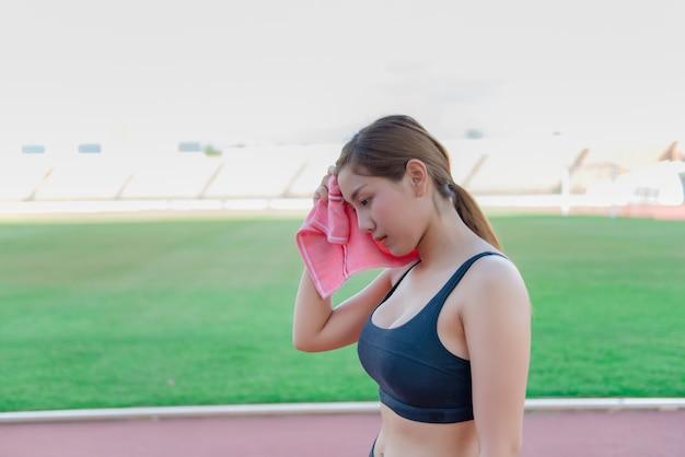 Сексуальные девушки прекращают вытирать пот после того, как бег заканчивается