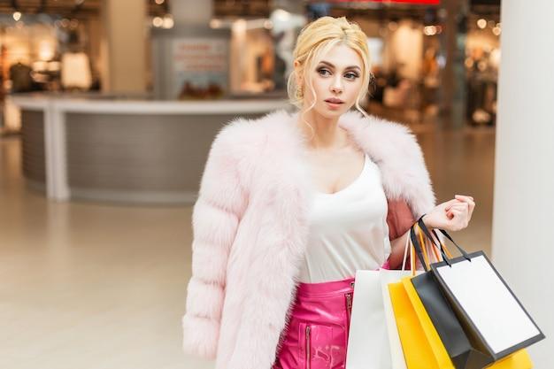 シックで高価なピンクの毛皮のコートでセクシーな魅力的な豪華な若いブロンドの女性