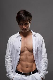 Сексуальный красивый азиатский мужчина-шоу с мышцей в студии.