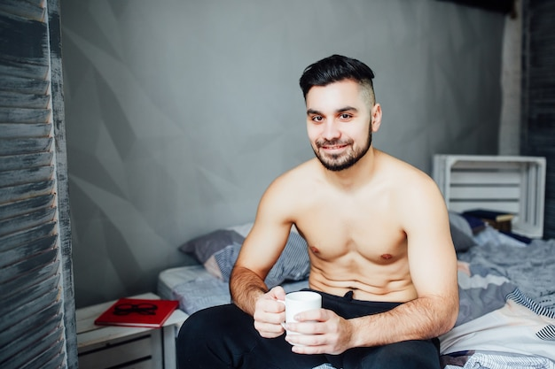 Sexy handsome young man laying shirtless on his bed, holding a coffee cup