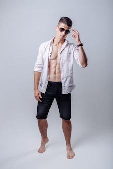 Сексуальный красивый молодой человек, стоящий в белой открытой рубашке и джинсовых шортах с улыбкой в солнечных очках.