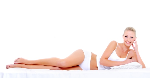 침대에 누워있는 몸의 완벽한 아름다운 모양을 가진 섹시한 행복한 여자