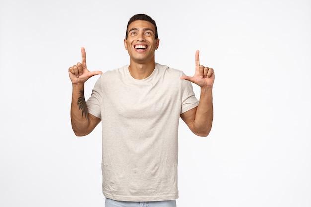 Sexy hispanic muscular male in casual t-shirt, looking up joyful