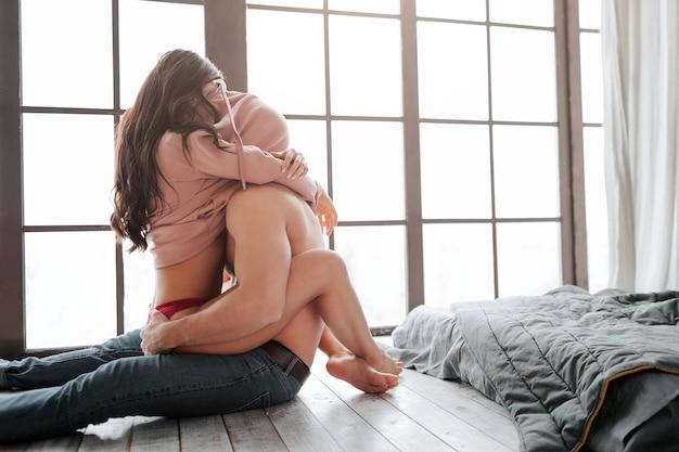 섹시 한 뜨거운 커플 방 바닥에 앉아. 그들은 스웨터 아래에 머리를 숨 깁니다. 젊은 여자는 남자에 앉아 다리와 손으로 그를 포용합니다.