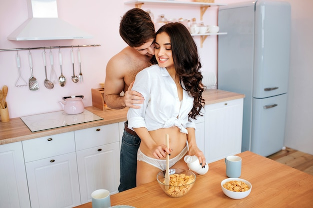 Sexy hot couple stand in kitchen. young woman hold spoon and bottle of milk in hands. guy stand behind her and kiss.