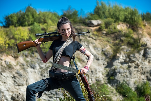 Sexy hunter with rifle posing outdoor, summer time