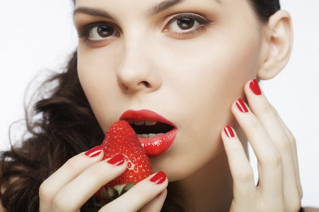 Sexy lady holding a juicy strawberry