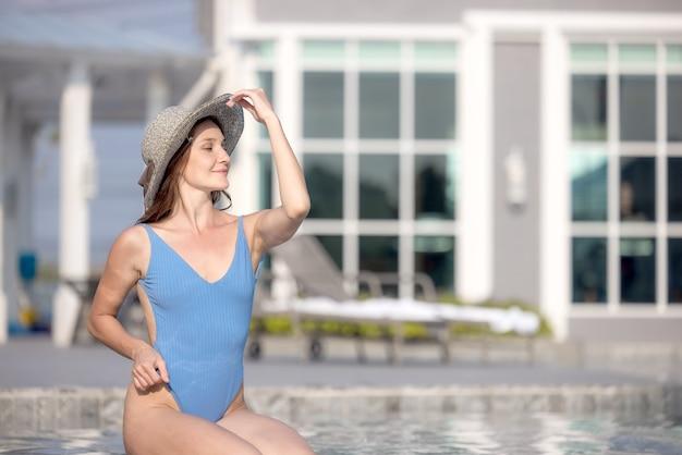 水プールを投稿するスイミングスイートのセクシーな女性。休日のコンセプトでリラックス