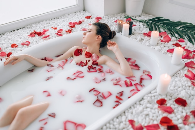 泡とバラの花びらとお風呂で横になっているセクシーな女性