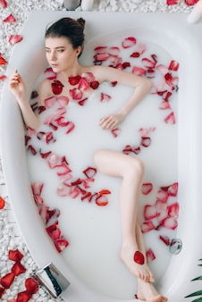 泡とバラの花びら、上面図でお風呂に横たわっているセクシーな女性。