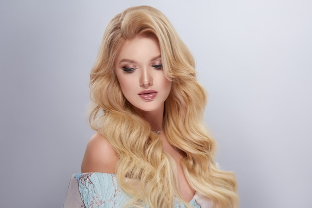 Sexy lady with volume hair and evening make-up looking down