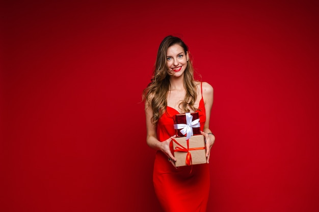 Sexy laughing woman in red with two presents.