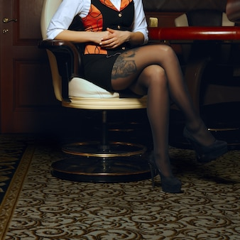Sexy legs of casino croupier in armchair