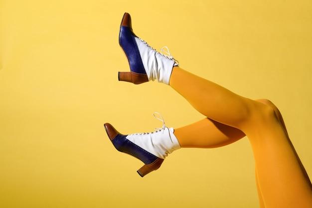 Сексуальные ноги женщины в чулках горчичного цвета и кожаных туфлях на шнуровке из тритона в стиле ретро