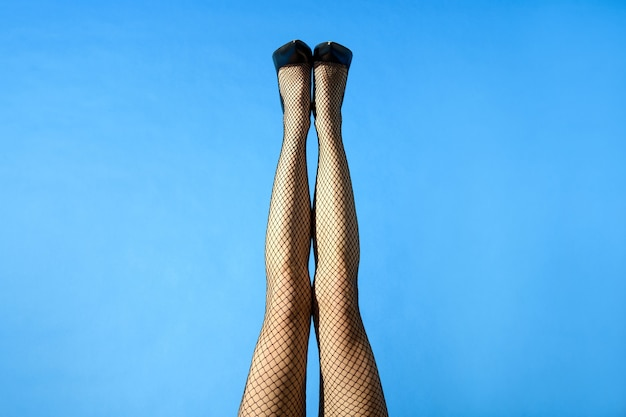 Sexy legs of a young woman wearing black fishnet stockings
