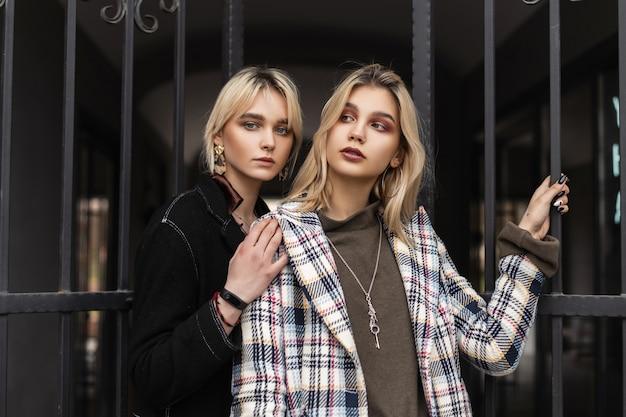 Сексуальные лесбиянки со светлыми волосами с красивыми губами с чистой здоровой кожей в модных куртках в стиле ретро гуляют по городу