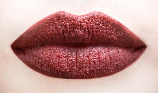 セクシーな唇。茶色の唇。ダークブラウンの口紅でセクシーな肉付きの良い唇のクローズアップ。