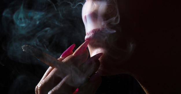Сексуальные губы, чувственный рот. сигаретные губы, сексуальное курение. курение сигареты, вихрь дыма, движение дыма. макрос части лица женщины. крупный план, высокое разрешение.