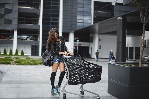 Сексуальная длинноволосая модель с идеальным стройным телом в шортах, чулках и кожаной куртке позирует с тележкой для покупок на открытом воздухе возле супермаркета