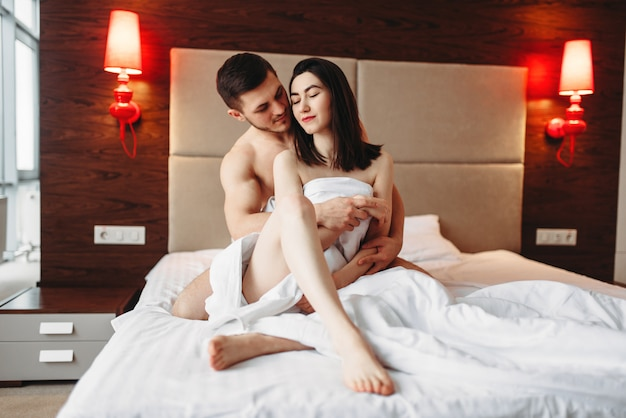 Sexy love couple hugging on big white bed after intimacy. intimate games in bedroom, sex lovers relationship