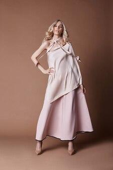 드레스에 섹시 한 고급 스러운 여자입니다. 가을 여성복 컬렉션. 배경에 포즈 긴 아름 다운 드레스에 패션 금발. 아름다운 머리와 완벽한 소녀상