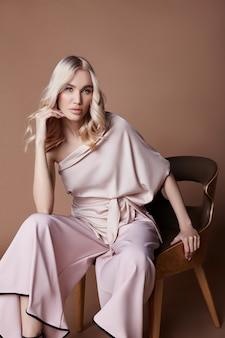자에 앉아 드레스에 섹시 한 고급 스러운 여자. 가을 여성복 컬렉션. 배경에 포즈 긴 아름 다운 드레스에 패션 금발. 아름다운 머리와 완벽한 소녀상