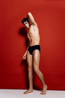 筋肉の筋肉を持つセクシーな男性アスリートボディービルダーフィットネス黒パンティー赤の背景の肖像画